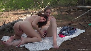 Teens share a dildo in outdoor scenes in front of the cam